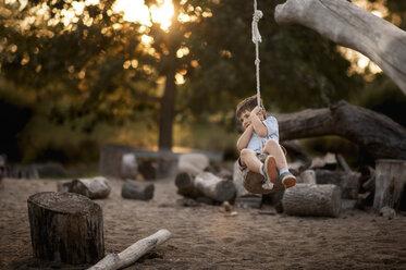 Playful boy swinging on rope swing at park - CAVF60431