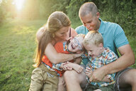 Happy family sitting on grassy field in forest - CAVF60458