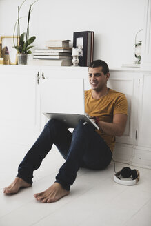 Smiling young man sitting on the floor using laptop - ERRF00364
