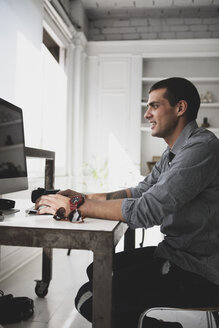 Young man sitting at desk using computer - ERRF00376