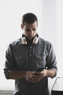 Young man with headphones using cell phone - ERRF00379