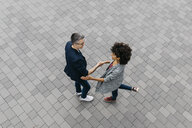 Top view of two colleagues shaking hands on a square - JRFF02214