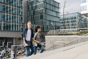 Two colleagues walking outside office building in the city - JRFF02217