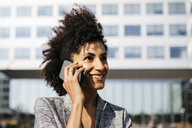 Portrait of smiling businesswoman on cell phone outside office building - JRFF02229
