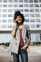 Smiling businesswoman on cell phone outside office building - JRFF02232