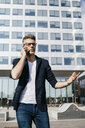 Angry businessman on cell phone walking outside office building - JRFF02235
