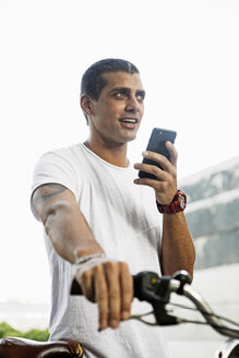 Young man with bicycle and cell phone on the go - ERRF00395
