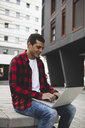 Young man sitting outdoors in the city using laptop - ERRF00401