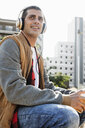 Smiling young man sitting outdoors in the city wearing headphones - ERRF00404