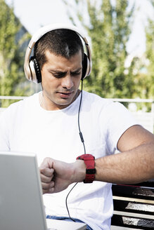 Young man with laptop sitting on a bench wearing headphones checking the time - ERRF00410