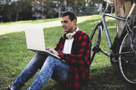 Young man sitting in a park using laptop next to bicycle - ERRF00416