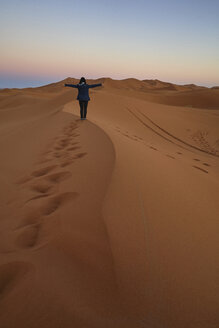 Morocco, back view of woman standing on desert dune at twilight - EPF00508