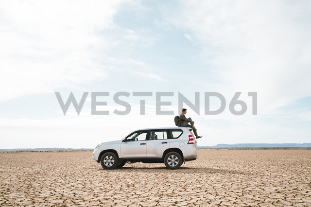 Side view of man sitting on off-road vehicle at barren landscape against cloudy sky - CAVF60499 - Cavan Images/Westend61