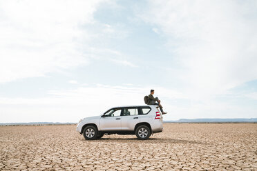 Side view of man sitting on off-road vehicle at barren landscape against cloudy sky - CAVF60499
