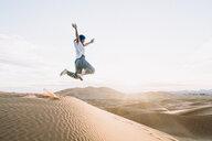 Happy woman jumping at Merzouga desert against sky - CAVF60511
