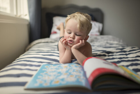 Boy with hands on chin reading picture book while lying on bed at home - CAVF60514