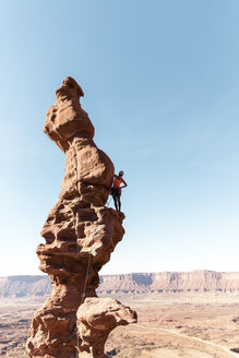 Female hiker standing on rock formation against clear sky during sunny day - CAVF60526
