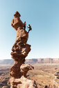 Female hikers with rope climbing on rock formation against clear sky during sunny day - CAVF60532