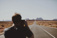 Rear view of hiker photographing landscape on country road against clear sky - CAVF60538