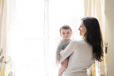 Portrait of cute son carried by mother against window at home - CAVF60619