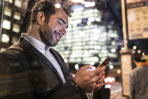 UK, London, businessman on the go checking his phone while commuting by night - WPEF01192