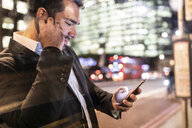UK, London, businessman on the go checking his phone while commuting by night - WPEF01195