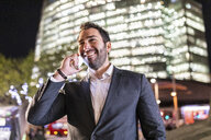 UK, London, portrait of smiling businessman talking on the phone while commuting by night - WPEF01198