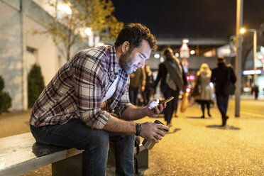 UK, London, smiling man sitting on a bench and looking at his phone by night - WPEF01204