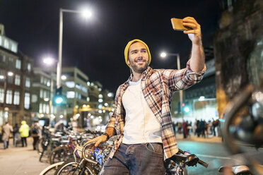 UK, London, man taking a selfie while commuting at night in the city - WPEF01210