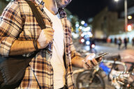 UK, London, close-up of man commuting at night in the city and using his phone - WPEF01213