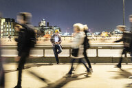 UK, London, man looking at his phone with blurred people walking on the pavement - WPEF01222