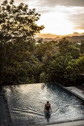 Philippines, Palawan, Coron, woman in swimming pool in the evening - DAWF00767