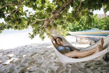 Philippines, Palawan, Mangenguey Island, Busuanga, woman lying in hammock at the beach - DAWF00773