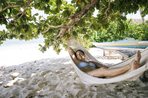 Philippines, Palawan, Mangenguey Island, Busuanga, woman lying in hammock at the beach - DAWF00773