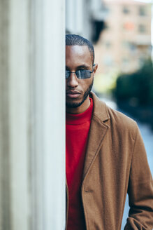Portrait of bearded young man with nose piercing and sunglasses hiding behind wall - JSMF00708