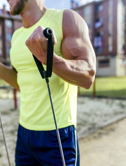 Close-up of muscular man exercising with expander outdoors - MGOF03846