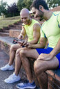 Two smiling athletes sharing smartphones after workout - MGOF03852