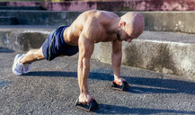 Barechested muscular man doing push-ups outdoors - MGOF03864