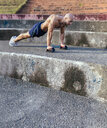 Barechested muscular man doing push-ups outdoors - MGOF03867