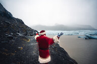 Iceland, back view of Santa Claus standing in front of glacier - OCMF00174