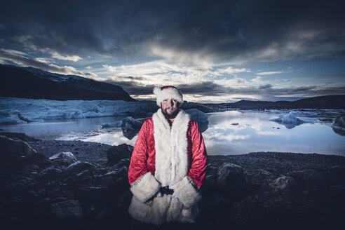 Iceland, portrait of Santa Claus standing in front of glacier - OCMF00177