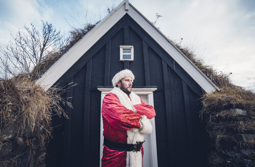 Iceland, Santa Claus standing in front of cabin looking at distance - OCMF00180
