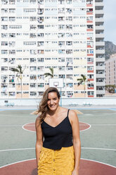 Hong Kong, Choi Hung, portrait of smiling woman at an apartment block - DAWF00794