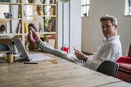 Portrait of businessman sitting with feet on desk - GIOF05071