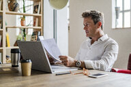 Focused businessman using laptop and reviewing documents at desk - GIOF05074