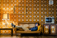 Man lying on couch in vintage living room - GIOF05077