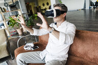 Mature man wearing VR glasses sitting on couch in a loft - GIOF05095