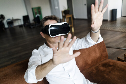 Mature man wearing VR glasses sitting on couch in a loft - GIOF05098