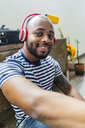 Portrait of smiling young man with headphones sitting on floor in a loft - GIOF05116