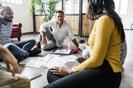 Business team sitting on floor discussing documents in loft office - GIOF05125